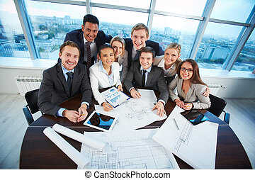 Happy co-workers - Group of business partners sitting at...