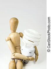 Compact Fluorescent Bulb - A wooden model grasping a compact...
