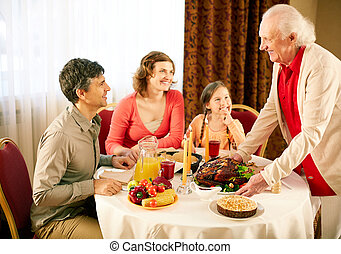 Gathered at dinner table - Portrait of happy family sitting...