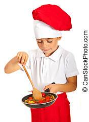 Boy preparing macaroni with tomatoes