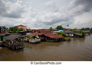 houseboat in Thailand - houseboat and river with blue sky in...