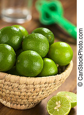 Limes in woven basket with lime squeezer and glass in the...