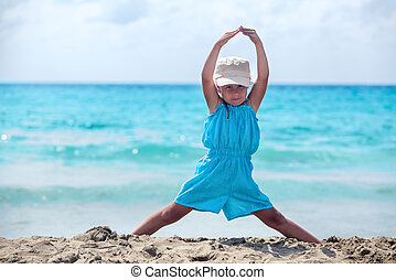 Small girl meditating in yoga pose standing on sandy sea...