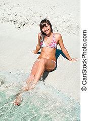 Beautiful woman sitting on white sand near sea water