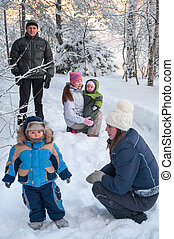 Women sisters with children and grandfather walking in winter forest