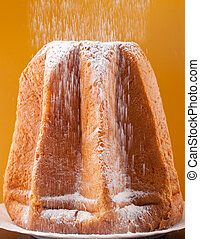 Pandoro with dusting of icing sugar on orange background
