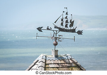 weather vane - metal weather vane over a hazy coastline