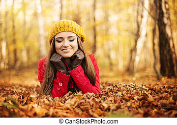 Smiling woman relaxing in the park at autumn
