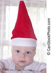 Funny baby in a red new year hat