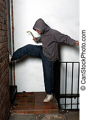 Break In - A man with a hooded pullover attempting to kick...