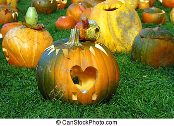 Halloween pumpkin with cutted out heart laid at the grass -...