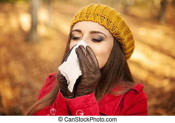 Woman sneezing in handkerchief at autumn