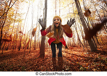 Young woman have fun with autumn leaves
