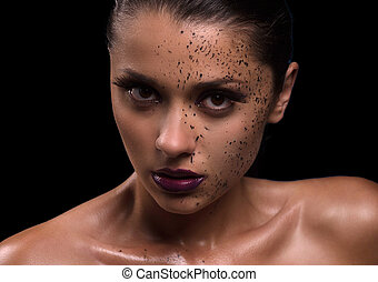 Beautiful naked woman. Portrait  of beautiful young woman looking at camera while standing against black background