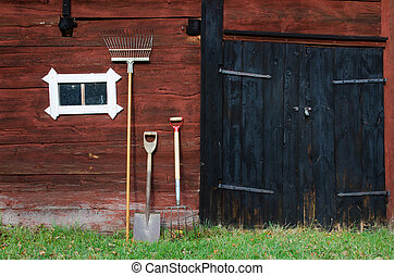 Old-fashioned - Garden tools at an old barn wall.