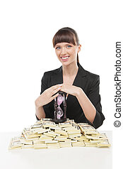 Time is money. Beautiful young businesswoman sitting at the table with a stack of money and hourglass on it