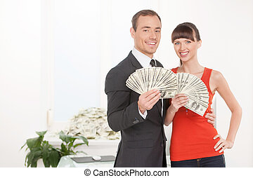 Successful couple. Happy young couple holding money in their...