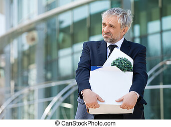 Fired. Depressed senior man in formalwear holding box with...