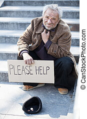 Please help. Depressed senior tramp in dirty wear sitting on...
