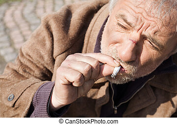 Tramp Top view of depressed senior man smoking