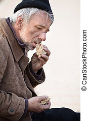 Homeless and hungry Side view of depressed senior man eating...