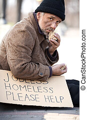 Homeless and hungry Close up of depressed senior man eating...