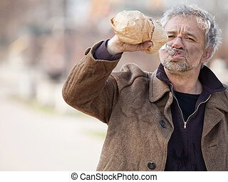 Homeless man drinking. Depressed senior man drinking alcohol...