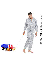 Big baby Young man in pajamas playing with toy car while...