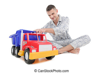 Big baby. Young man in pajamas playing with toy car while sitting isolated on white