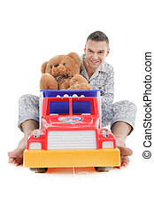 Big baby. Young man in pajamas playing with toy car and teddy bear while sitting isolated on white