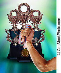 gold cup championship and hand holding gold medal