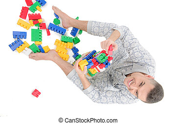 Big baby. Top view of young man in pajamas playing toys while isolated on white