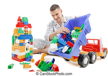Big baby Excited young man in pajamas playing toys while...
