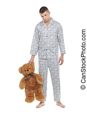 Man with teddy bear. Young man in pajamas holding teddy bear...