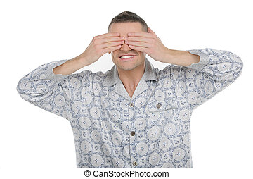 Man clothing eyes. Cheerful young man in pajamas clothing...