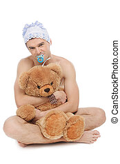 Man in diaper. Infant adult man in diaper holding teddy bear and looking at camera while sitting isolated on white