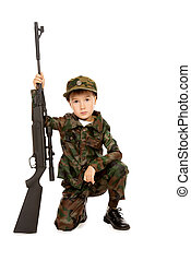 serious - A boy dressed like a soldier standing with a rifle...