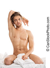 gorgeous - Handsome nude man sitting on a bed Isolated over...