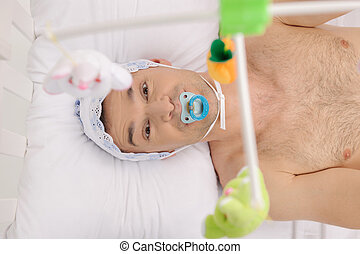 Big baby. Top view of infant adult man with pacifier looking at camera while lying on the baby bed
