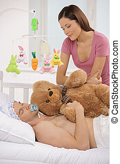 Big baby in bed. Infant adult man lying on the baby bed while young woman looking at him