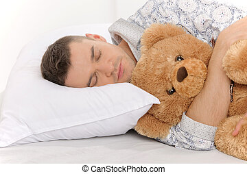 Big baby with Teddy Bear. Infant adult man sleeping with his teddy bear