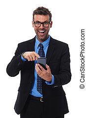 Happy and surprised businessman pointing at mobile phone