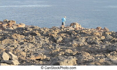 man sitting on the edge of a cliff - A wide shot of man...