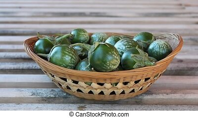 thai round eggplant - filling a wicker basket with eggplant...