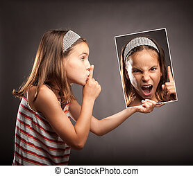 little girl showing silence gesture and holding a portrait...