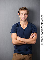 Confident casual unshaven young man standing with his arms...