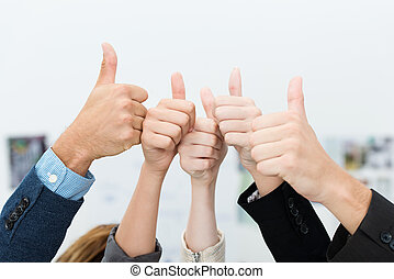 Business team giving a victorious thumbs up - Successful...
