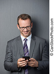 Businessman smiling while using the smartphone