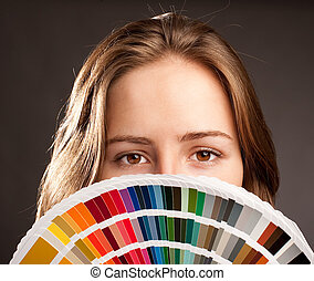 woman with pantone - young woman holding a pantone palette