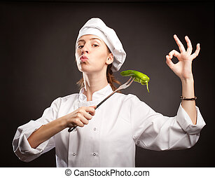 woman chef holding a green pepper with a fork